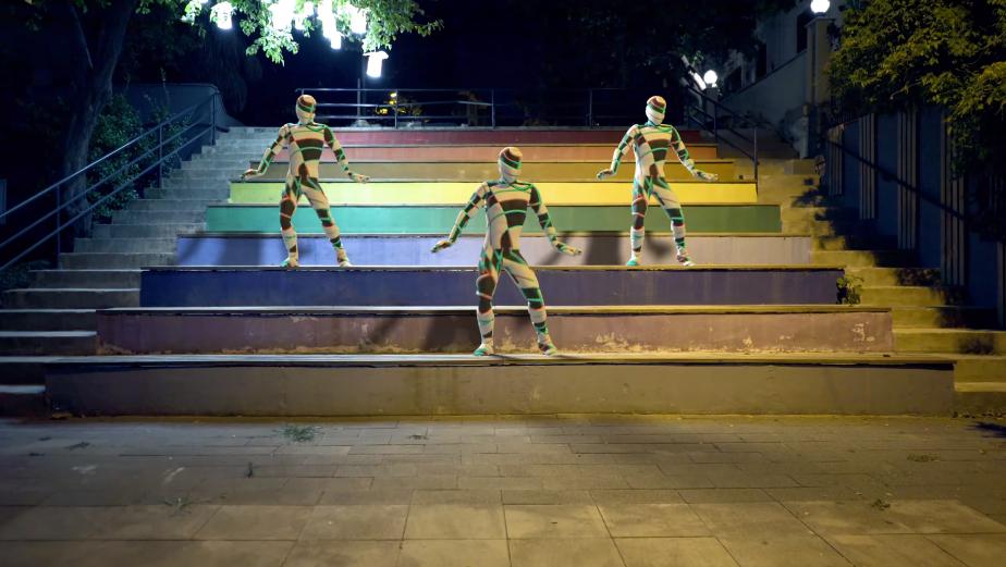 Bailarines de CGI que reinventan el baile. Vestido de colores, danzan en un parque.