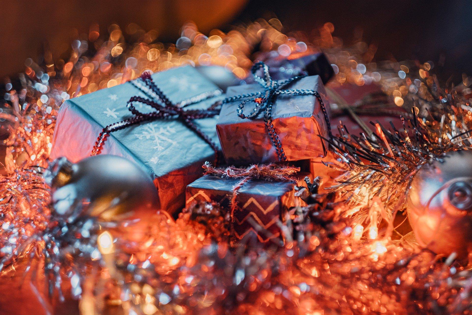 Unos regalos relucientes entre adornos navideños.